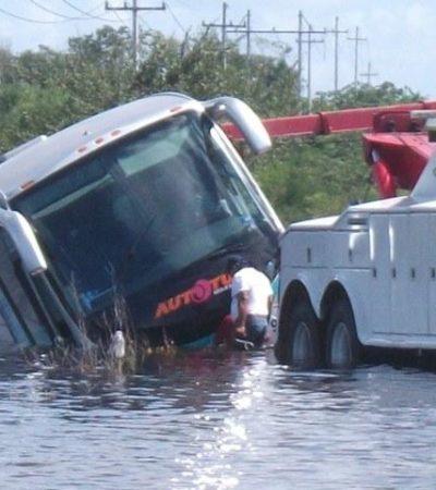 Por inundación en carretera en Lázaro Cárdenas, autobús turístico termina en una laguna