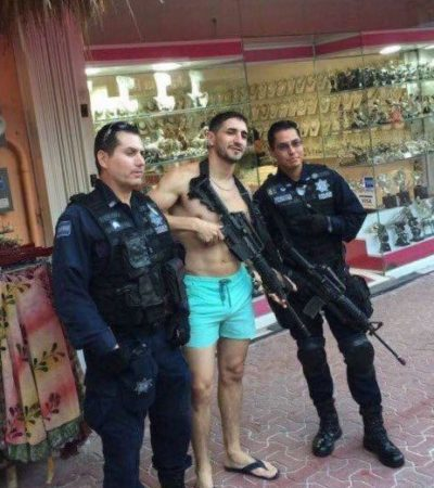 Policías federales le prestan su arma a un turista y se toman la foto del recuerdo en la Quinta Avenida de Playa del Carmen