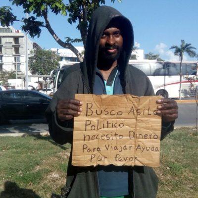 Con un cartón garabateado en Cancún, estadounidense pide asilo en México