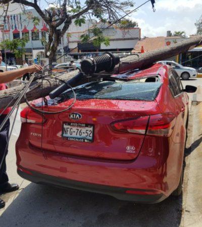 Cae poste de telefonía sobre vehículo en Cancún