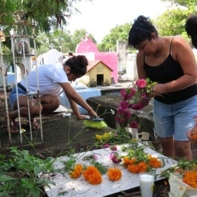 """Rodeados de Cempasúchil, veladoras e incienso, familiares preparan tumbas de sus seres queridos para recibirlos como cada año en el panteón """"Los Olivos"""" de Cancún"""